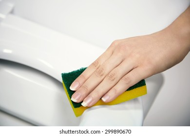 Bathroom cleaning concept, young woman cleaning a toilet seat with a sponge, closeup view of the hand