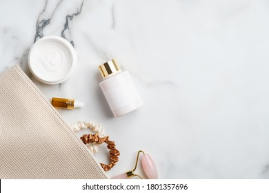Bathroom cosmetic bag with moisturizer cream, lotion, face massage roller, essential oils bottles and female accessories on marble desk. Beauty products set. Flat lay, top view.