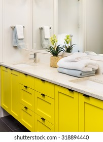 Bathroom detail in new luxury home: colorful yellow vanity with cabinet, mirror, counter, sink, and faucet, decorated with towels