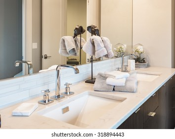Bathroom detail in new luxury home: vanity with cabinet. Dual sinks and counter decorated with towels