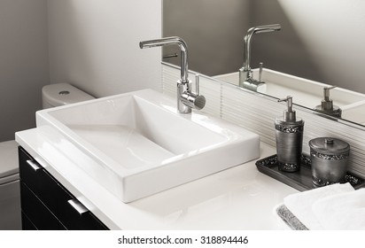 Bathroom detail in new luxury home: sink and faucet with partial view of toilet