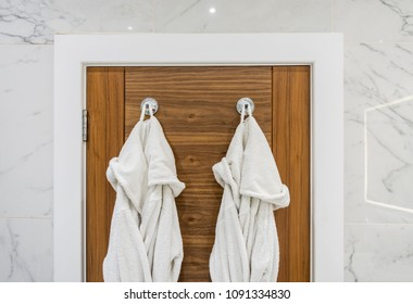bathroom door detail with bathrobes on marble wall