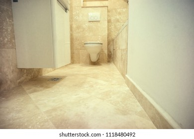 Bathroom floor/Low angle shot of a bathroom interior with floating like suspended toilet and sink over a marble flooring.
