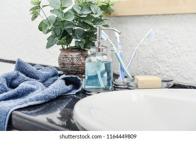 Bathroom with glass liquid soap dispenser, tooth brushes and towels closeup