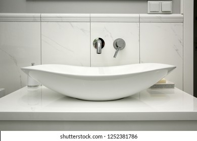 The bathroom has a modern style and marble tiles.
