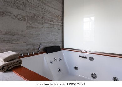 Bathroom hotel interior: huge hydromassage acrylic bathtub with towels