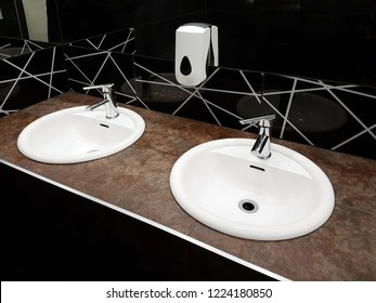 Bathroom interior in black and white. Round ceramic washbasins. Mirrors, plastic soap dish and chrome faucets for washing hands after a toilet. Design with dark facing tiles.