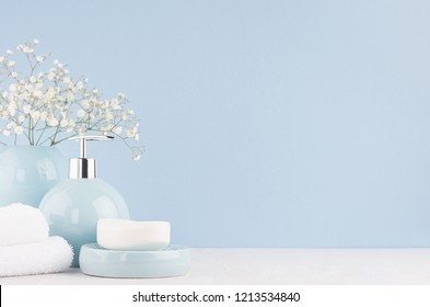 Bathroom interior - ceramic accessories - light blue circle vase with white flowers, soap dispenser , fluffy towels on white wood table.