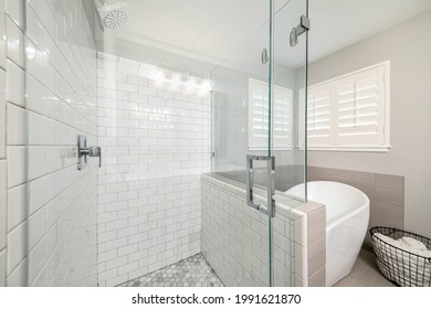 Bathroom interior with frameless shower stall and freestanding bathtub. Stall with subway tile walls and wall mounted shower head beside the tub with towel storage basket against the jalousie windows.