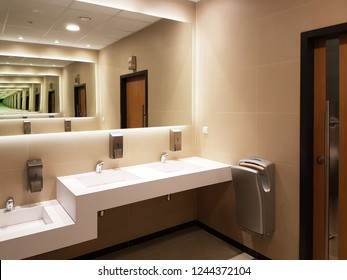 Bathroom interior in light beige and white colors. Round ceramic washbasins. Mirrors, plastic soap dish and chrome faucets for washing hands after a toilet. Design with dark facing tiles.