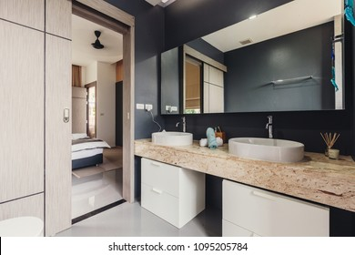 Bathroom interior in luxury modern villa, grey colours, open door coupe, view to bedroom