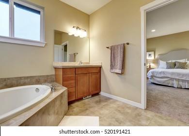 Bathroom interior with vanity cabinet and bathtub in the corner. Open door to master bedroom. Northwest, USA