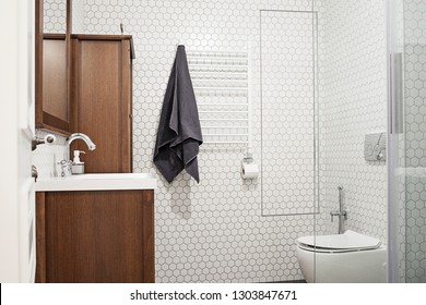 Bathroom interior with white mosaic wall, wooden frame mirror, sink, faucet and wooden Cabinet .