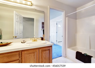 Bathroom interior in white tones with brown cabinets, white bath tub and tile floor