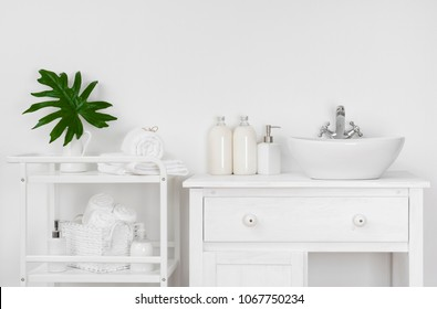 Bathroom interior with white wall, vintage furniture, towels and sink