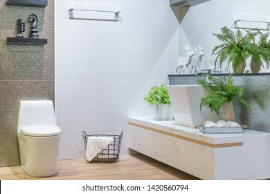 Bathroom interior with white wall, vintage furniture, towels, toilet and sink