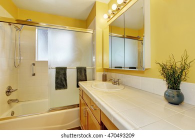 Bathroom interior in yellow tones and tile counter top. Northwest, USA
