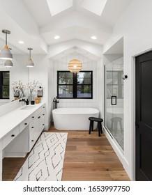 Bathroom in luxury home with double vanity, bathtub, mirror, sinks, shower, and hardwood floor