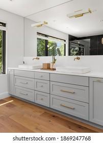 Bathroom in luxury home with double vanity, mirror, sink, and tile floor