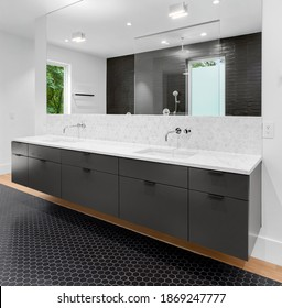 Bathroom in luxury home with double vanity, mirror, sink, and tile floor.Large walk-in shower is visible in mirror reflection.