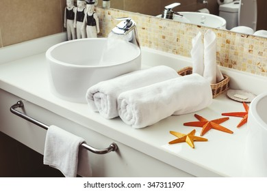 Bathroom Luxury interior. White towels, tropical decor. Water flow from tap