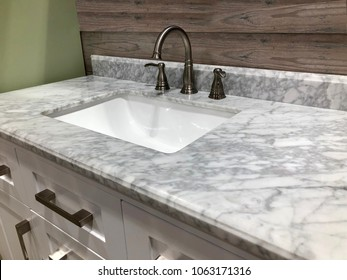 Bathroom marble countertop with white sink, chrome faucet and white cabinets