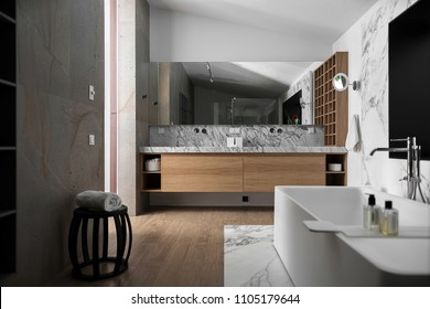Bathroom in a modern style with light walls. There is a tiled zone with a white bath with chrome faucet, sink with mirror and lockers and niches, wooden shelves, dark chair with a white towel.