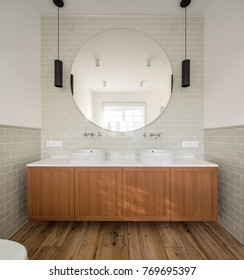 Bathroom in a modern style with light walls with tiles. There is a wooden rack with two white sinks with chrome faucet, big round mirror over them, black hanging lamps, toilet. Vertical.