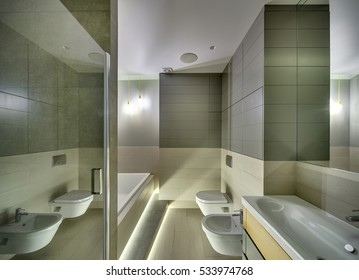 Bathroom in a modern style with tiles on the walls and floor. There is a sink with a faucet, white toilet and a bide, white bath, glass door, mirror, glowing lamps. Horizontal.