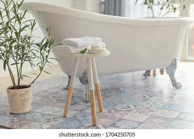 bathroom in modern style, towel on stool a front of white bath in botanical style room