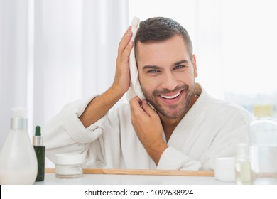 In the bathroom. Nice cheerful man holding his towel while wiping his face