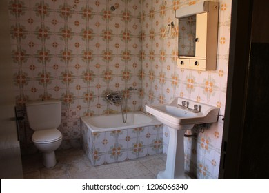 Bathroom in old house with white and orange antique tiles