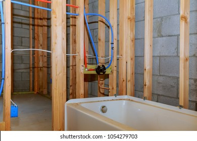 Bathroom remodel showing under floor plumbing work connecting installation of pipes for water for new buildings