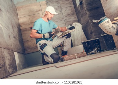 Bathroom Remodeling by Men. Caucasian Ceramic Tiles Installer During His Working Hours. Wooden Like Tiles.