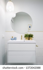 Bathroom with round mirror and white cabinet with drawers