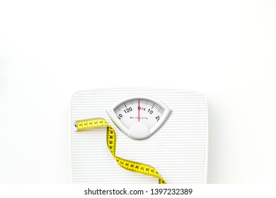 bathroom scales and measuring tape for weight loss concept on white background top view space for text