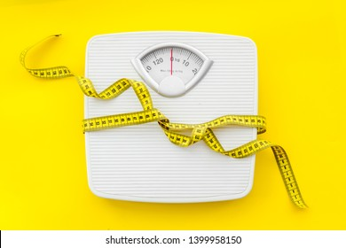 bathroom scales and measuring tape for weight loss concept on yellow background top view