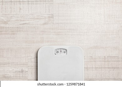 Bathroom scales and space for text on wooden background, top view. Weight loss concept