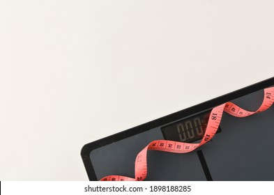 Bathroom scales and tape measure on white background. Selective focus.
