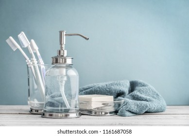 Bathroom set with toothbrushes, towel and soap on blue background