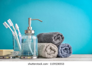 Bathroom set with toothbrushes, towels and soap on blue background