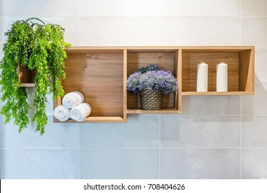 Bathroom set with towels, flower and green plant on a shelf in light interior