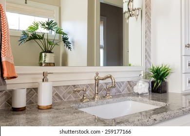 Bathroom sink with mirror and upscale countertop in new luxury home