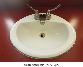 bathroom sink with red countertops