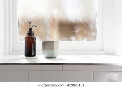 Bathroom soap dispenser and pot on window ledge with background of negative space horizontal