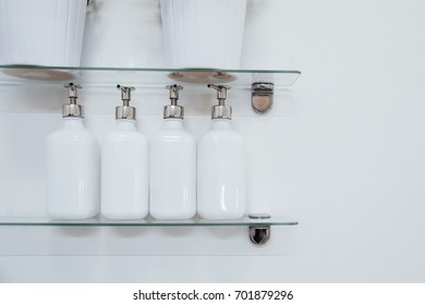 Bathroom soap dispenser and pot on shelf with white background of negative space horizontal. White ceramic bottles with liquid soap or shower gel at hotel.