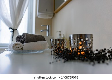 Bathroom still life of rolled towels and burning candles in cut out patterned metal candle holders on a vanity alongside the hand basin in a low angle view conceptual of personal hygiene