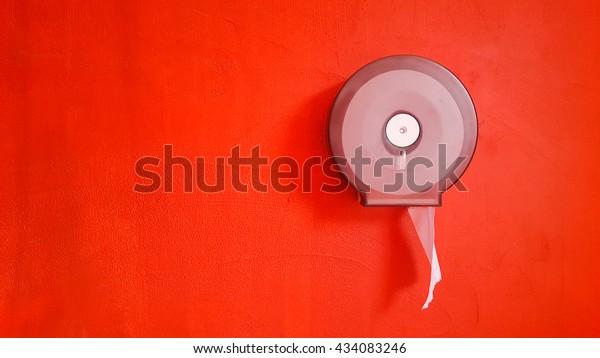 Bathroom tissue hanging box on orange concrete wall, Toilet paper .Trash