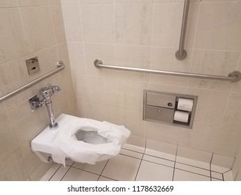 bathroom toilet with paper and metal railings