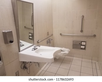bathroom toilet with paper and metal railings and sink